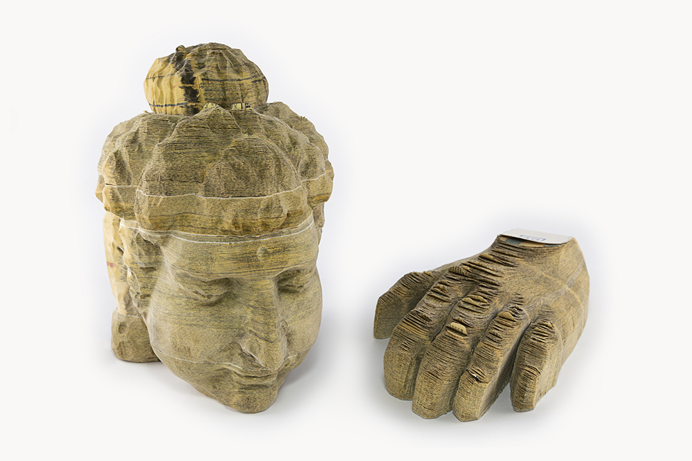 Long-Bin Chen - Indian Buddha and Hand (SOLD), 2006-2007, carved telephone books in two parts, head: 8 by 5 by 5.5 inches; hand: 2 by 5 by 7.75 inches
